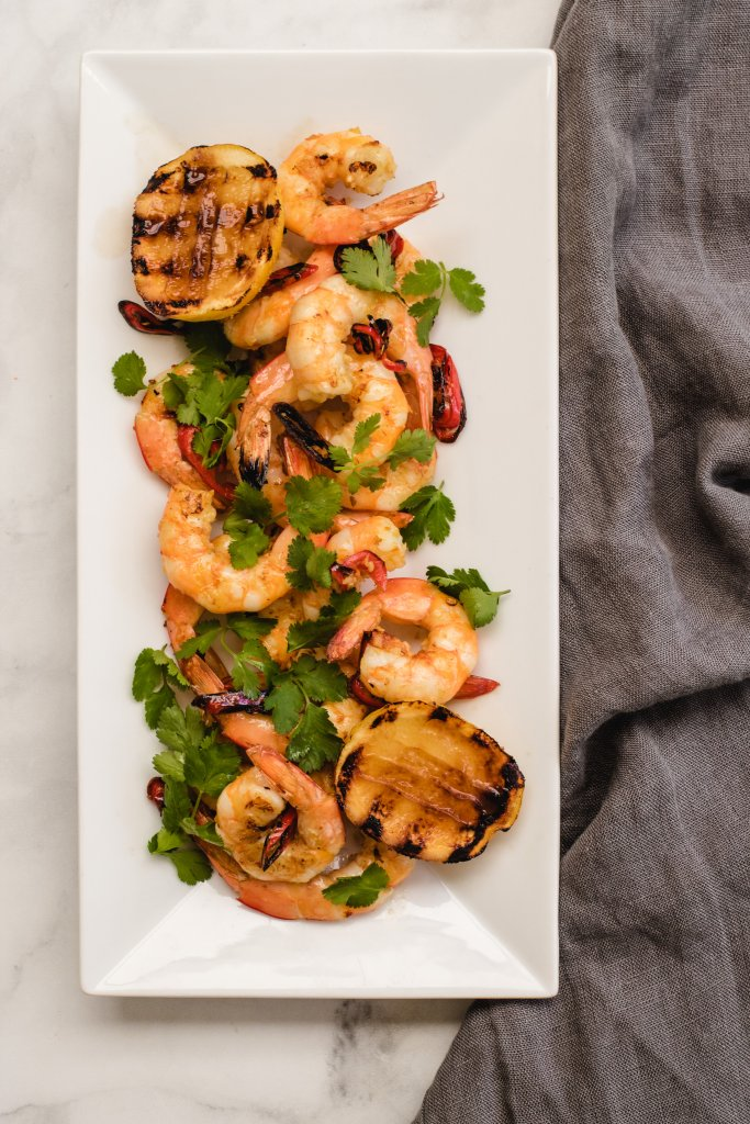keto prawns on a white rectangle serving dish with a grey linen cloth on a white background