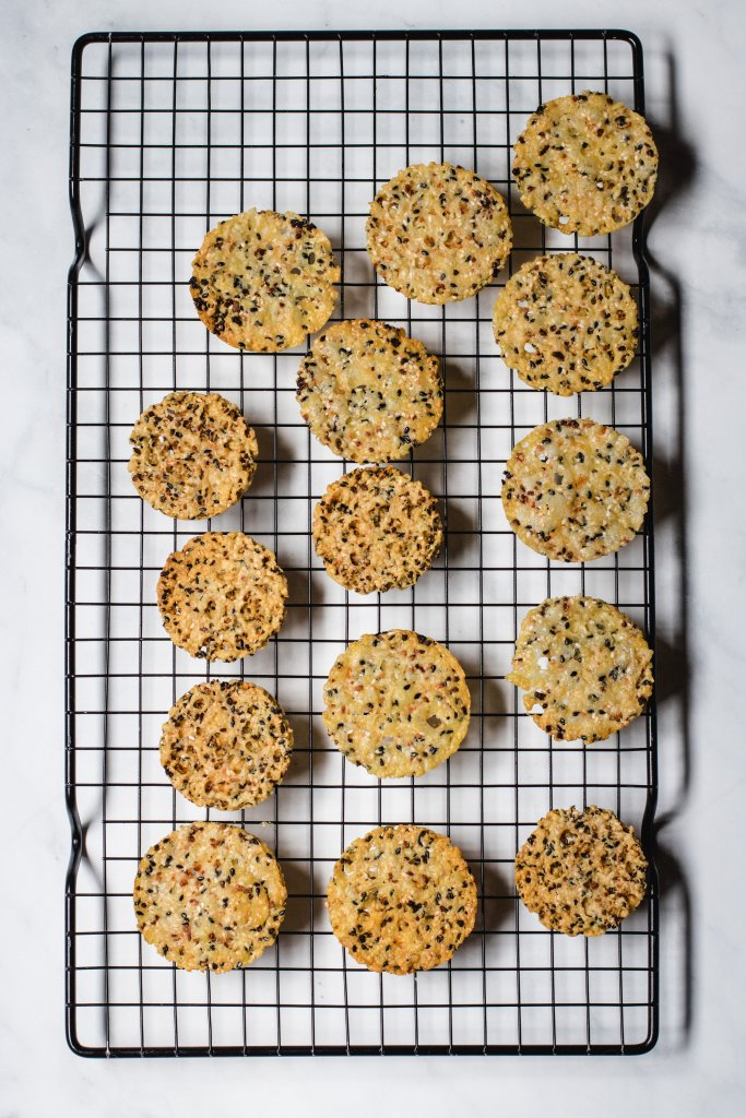 Everything but the bagel cheese crisps on a black cooling rack on a white background