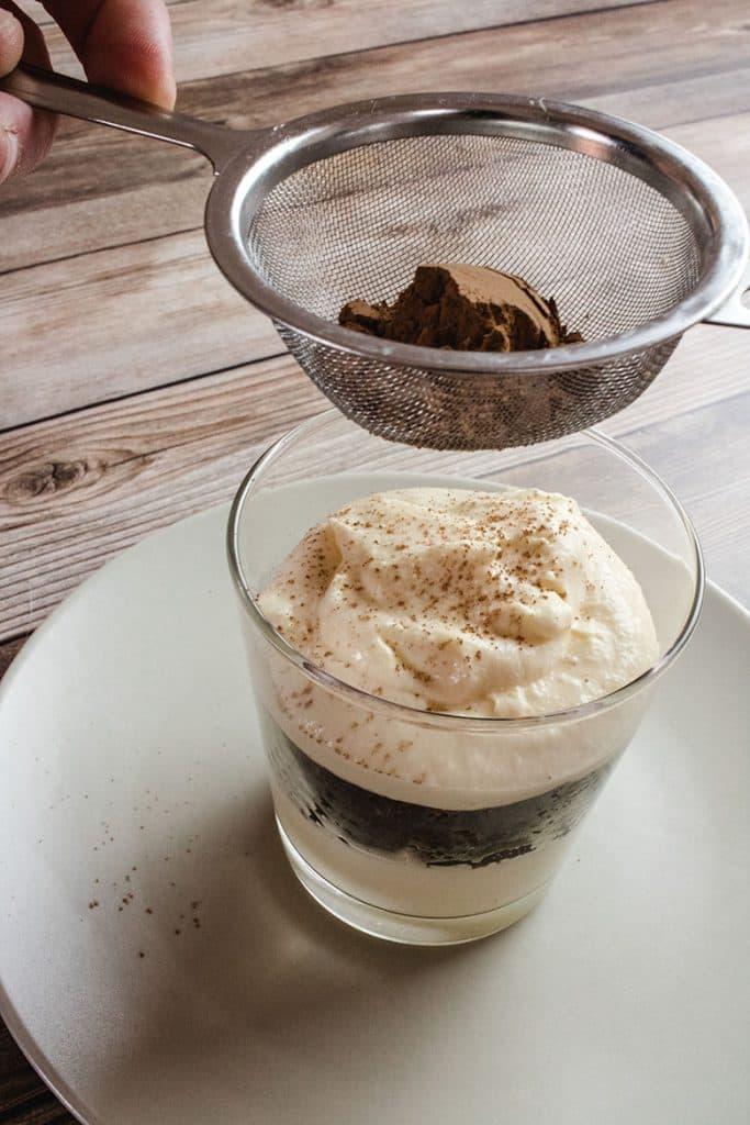 Keto tiramisu with tea strainer above dusting cocoa powder onto the cream.