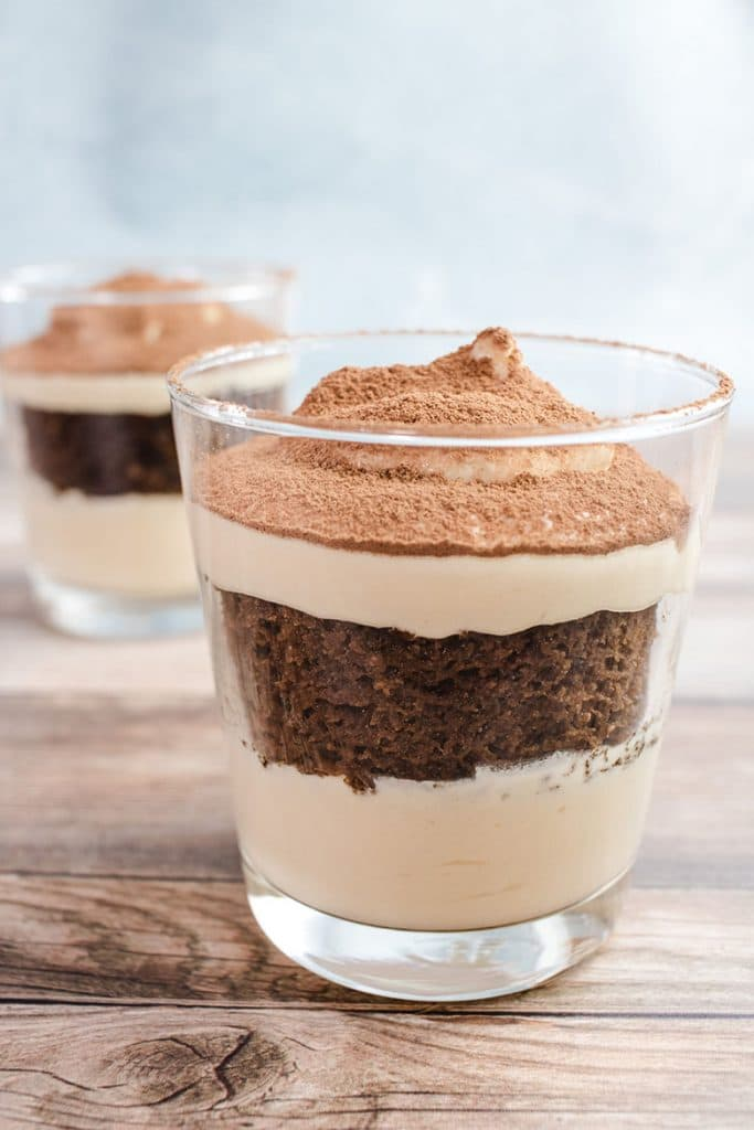 Keto tiramisu in a small drinking glass with another keto tiramisu in the background.
