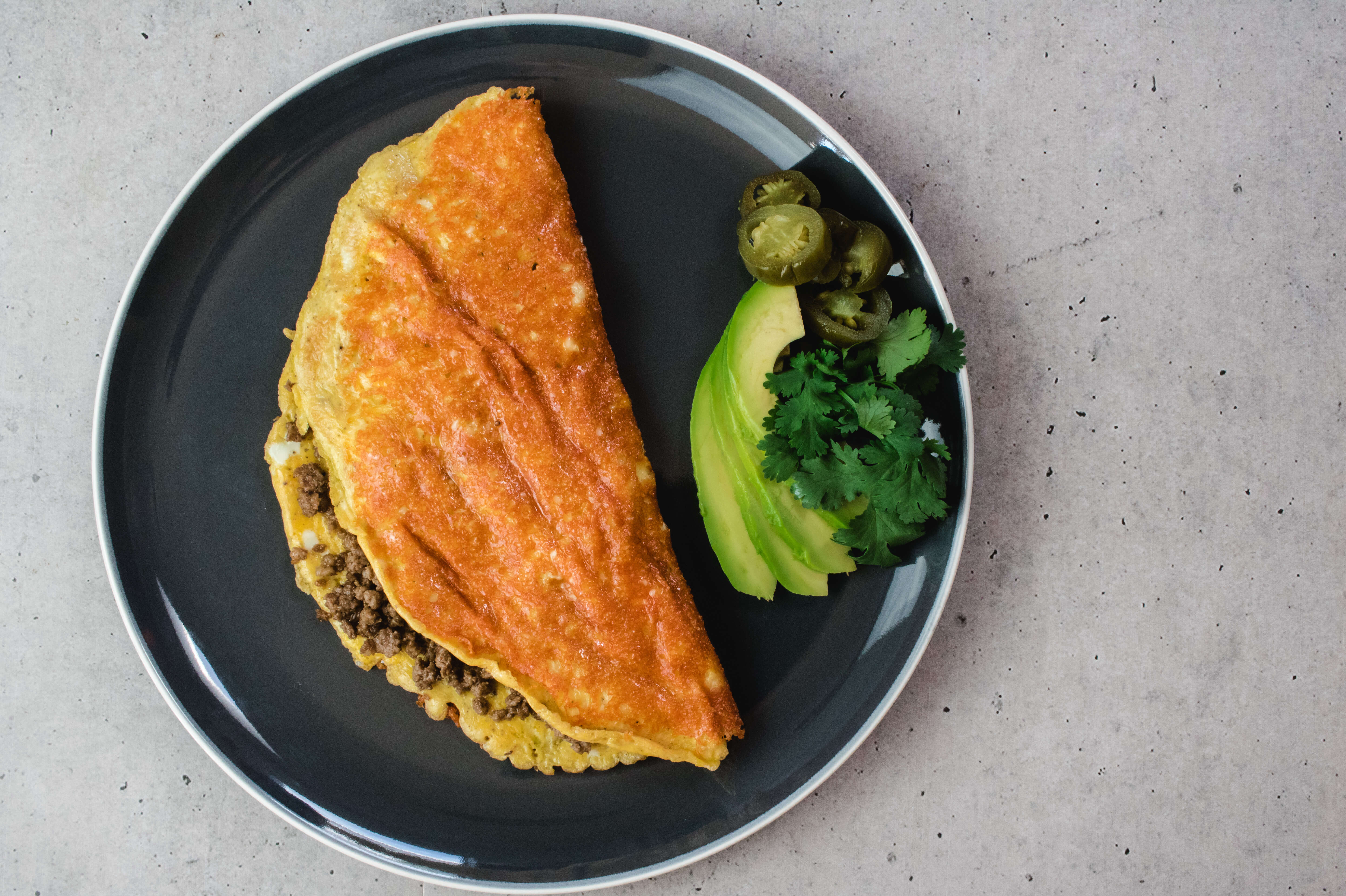 This Mexican inspired cheesy taco omelette is easy to make and delicious. It is a perfect low carb breakfast, but works just as well for Lunch and Dinner.