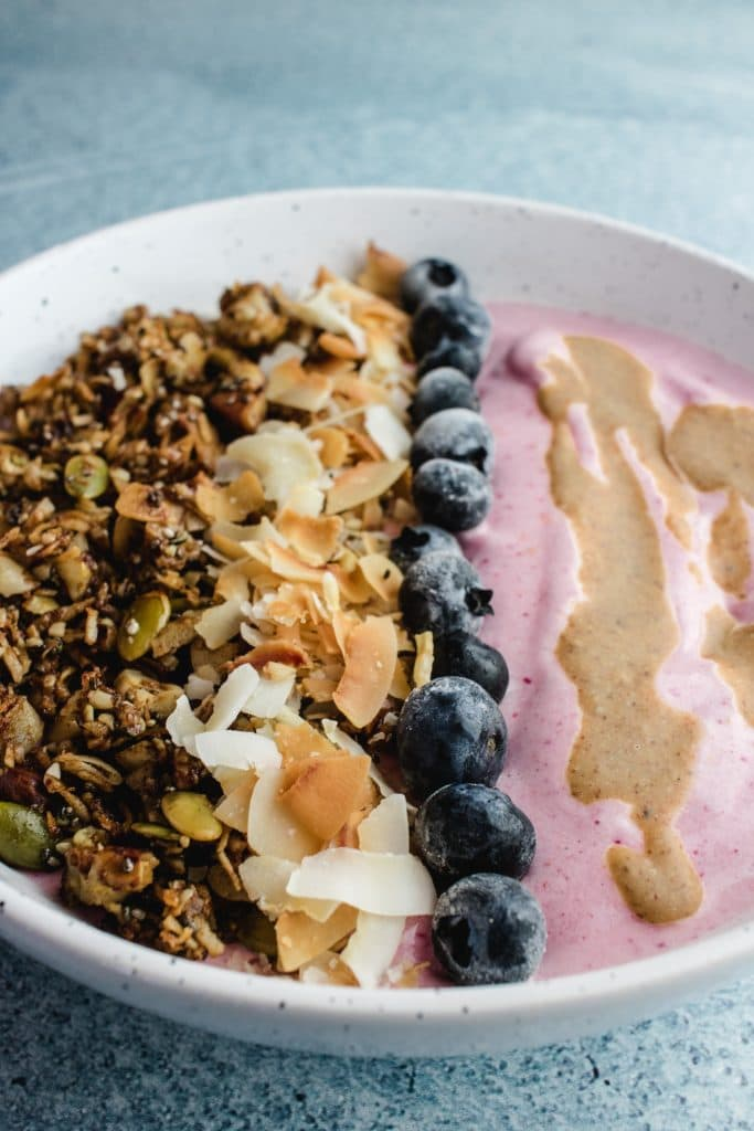 Strawberry smoothie bowl in a white speckled bowl topped with almond butter, blueberries, coconut flakes and granola. The toppings are all neatly in a line.