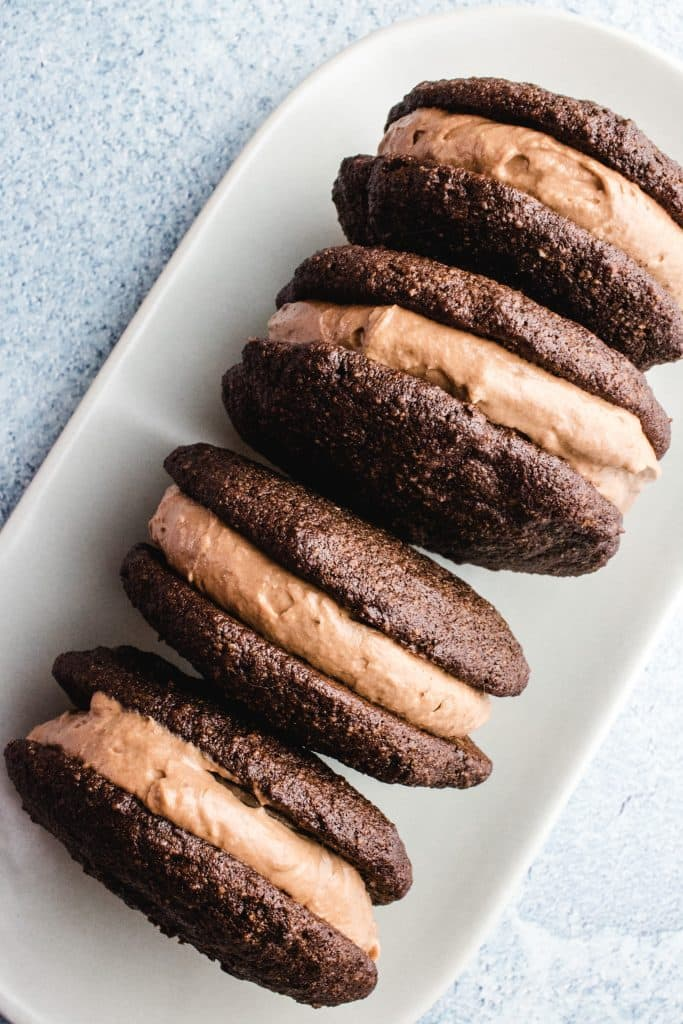4 chocolate whoopie pies standing on their edge and leaning against each other.