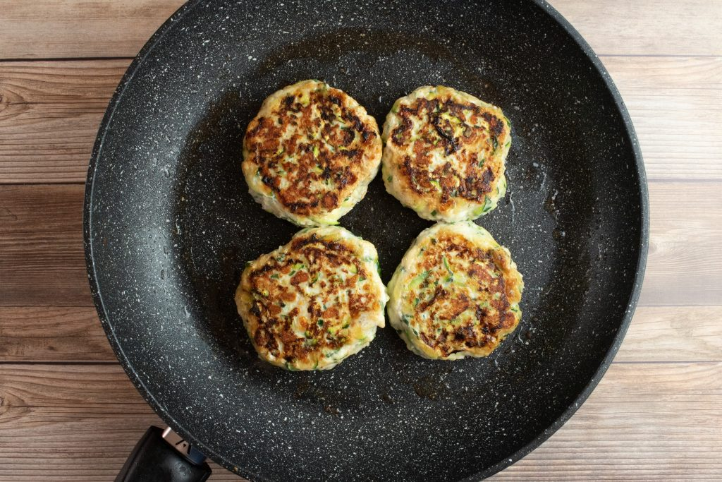 4 keto chicken burgers in a frying pan with a timber background