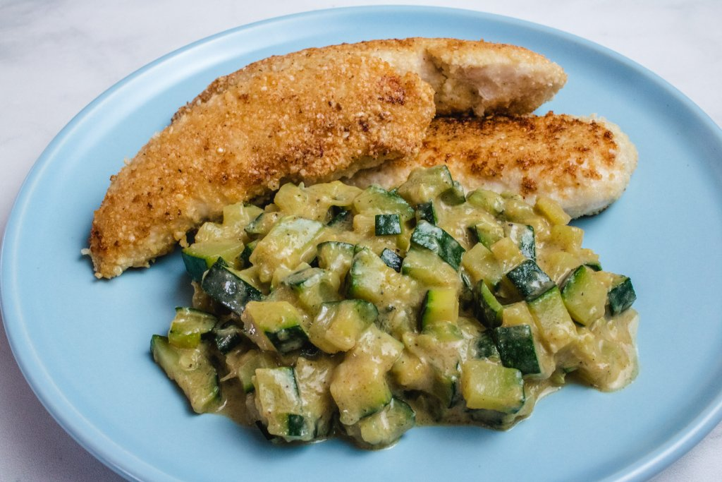 Curried zucchini and crumbed chicken on a blue plate.