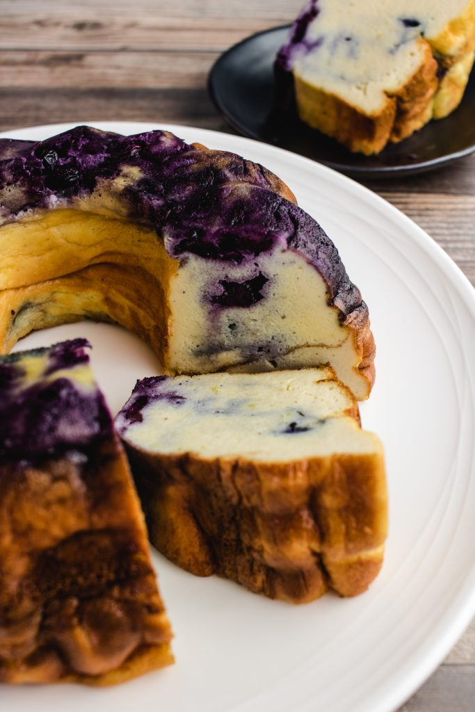 Blueberry egg loaf with 2 peices cut out, one cut piece in the middle and one cut piece in the background