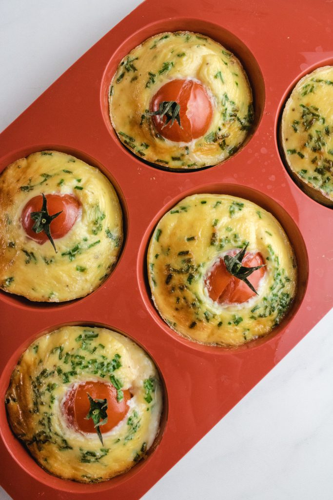 5 keto egg muffins inside their muffin tray. Then muffin tray is red
