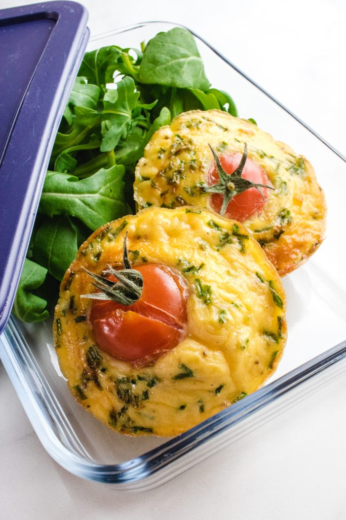 2 keto egg muffins in a glass container with some rocket and a blue plastic lid