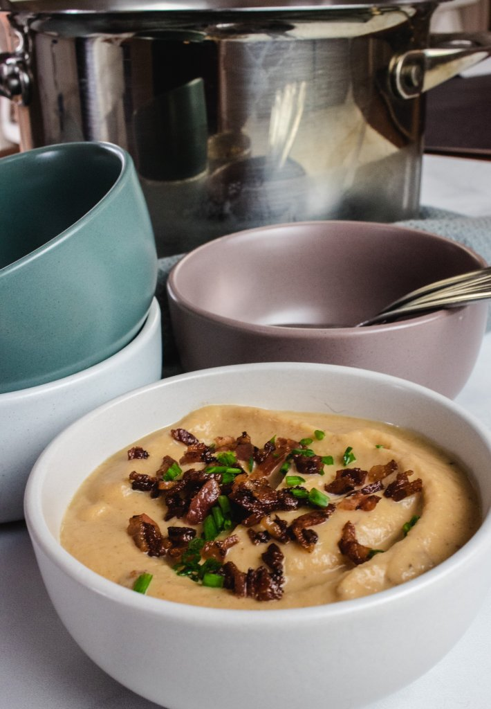 Cauliflower soup in a white bowl with bacon and chive on top. Three bowls with spoons in behind it and a saucepan behind that