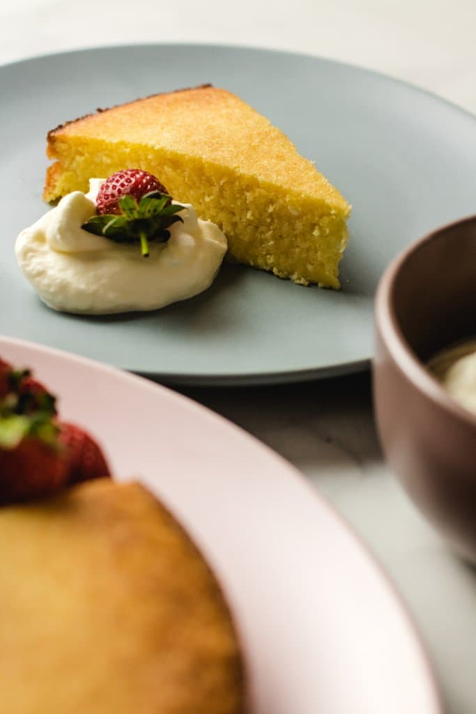 One piece of lemon cake on a blue plate with a dollop of cream and a strawberry