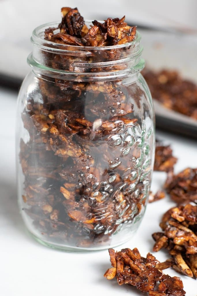 A jar of keto granola with granola scattered around the jar and a tray of granola in the background.