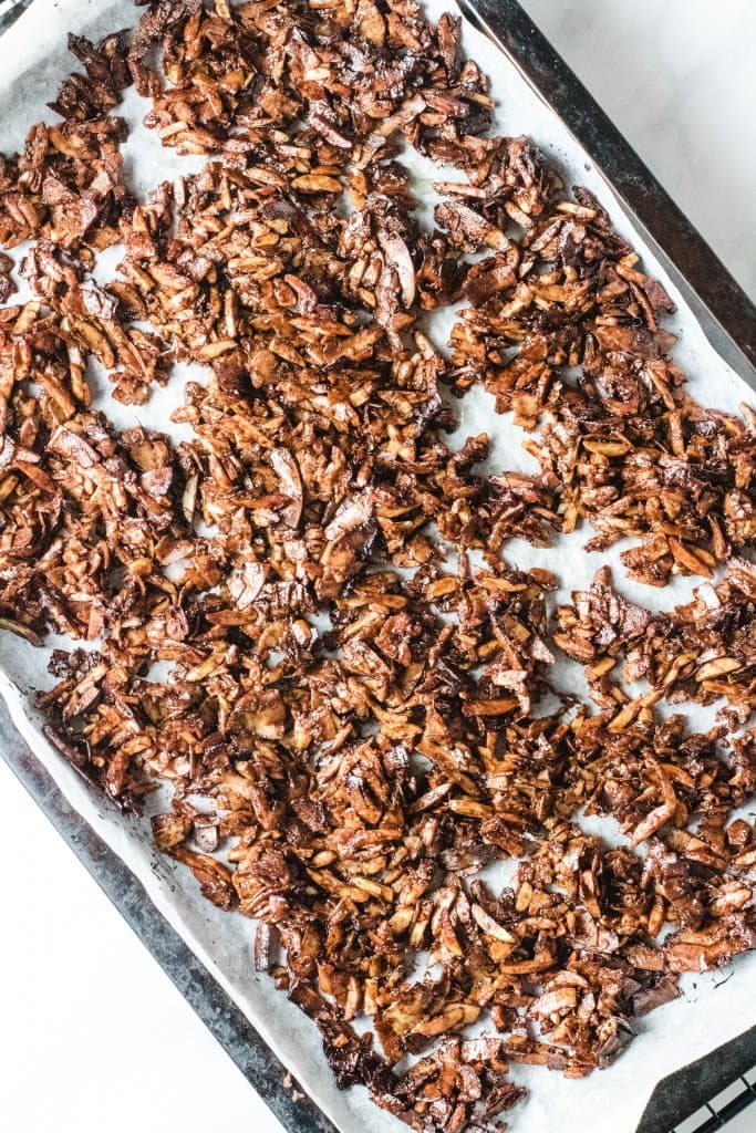 Keto granola on a baking tray under some baking paper