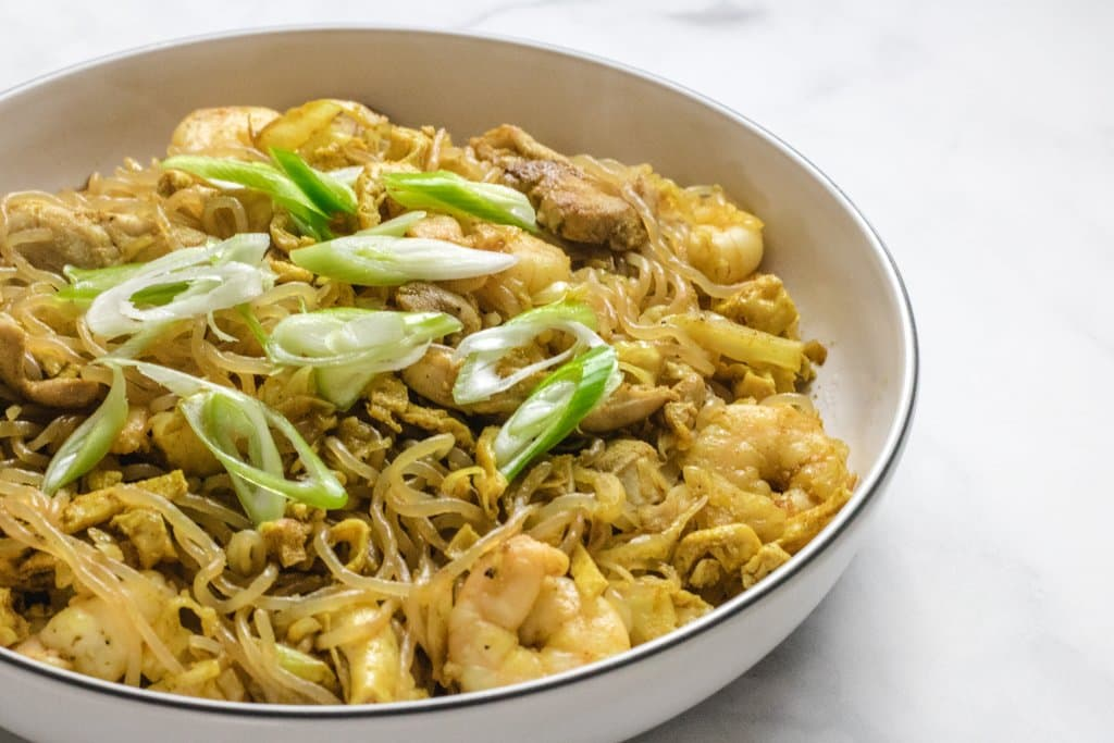Singapore noodles in a white bowl on a white marble background