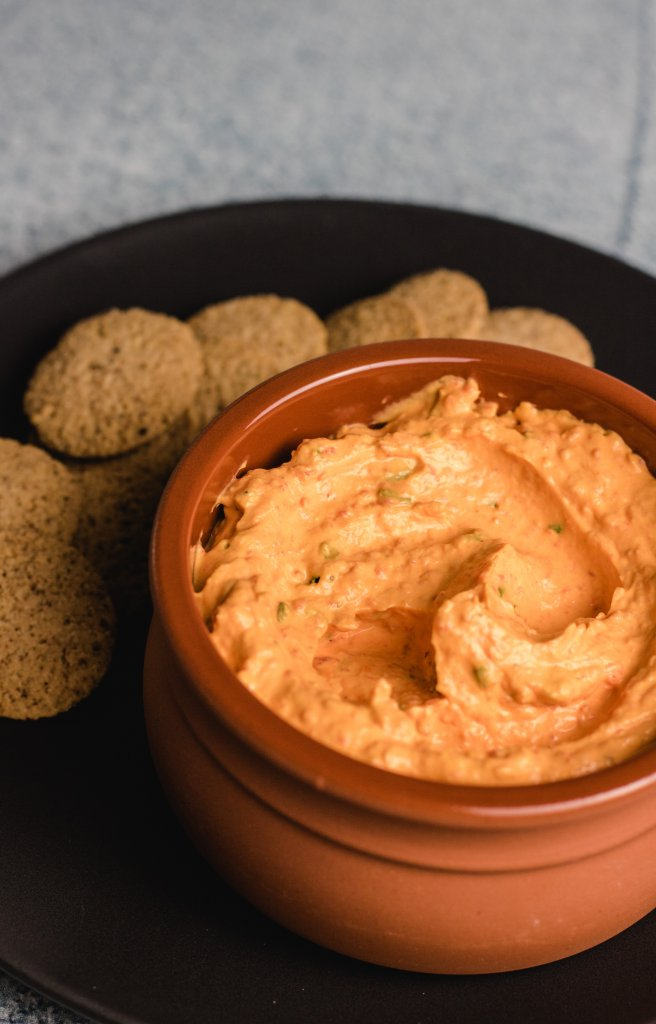 Roasted capsicum dip in a terracotta bowl sitting on a black plate with round crackers beside the dip.