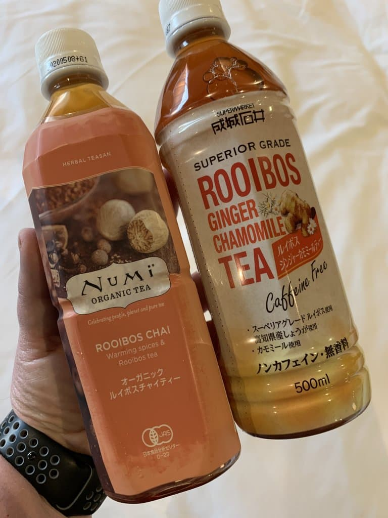 hand holding a rooibos chai anf ginger chamomile iced tea