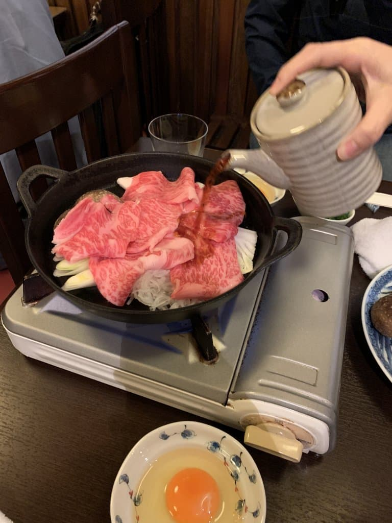 Pan of raw wagyu beef in a pan on a cooktop with broth being poured in from a tea pot with a raw egg in the foreground