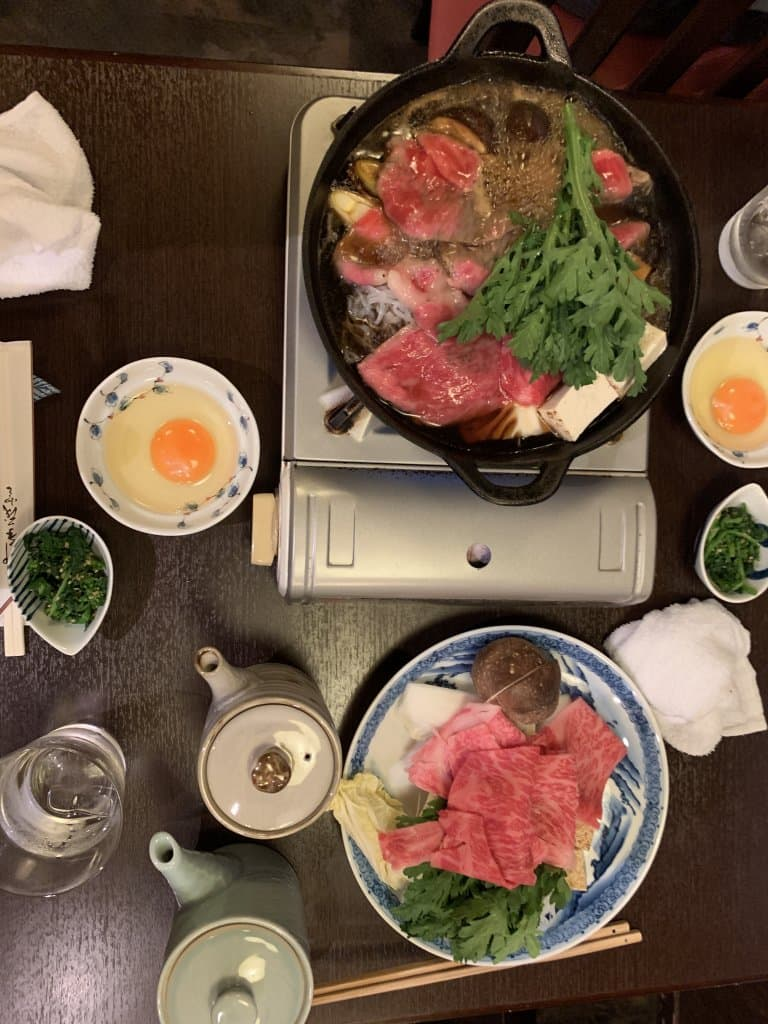 Sukiyaki in a pan with two bowls of cracked eggs, and a plate of raw sukiyaki ingredients on a plate with 2 Japanese tea pots
