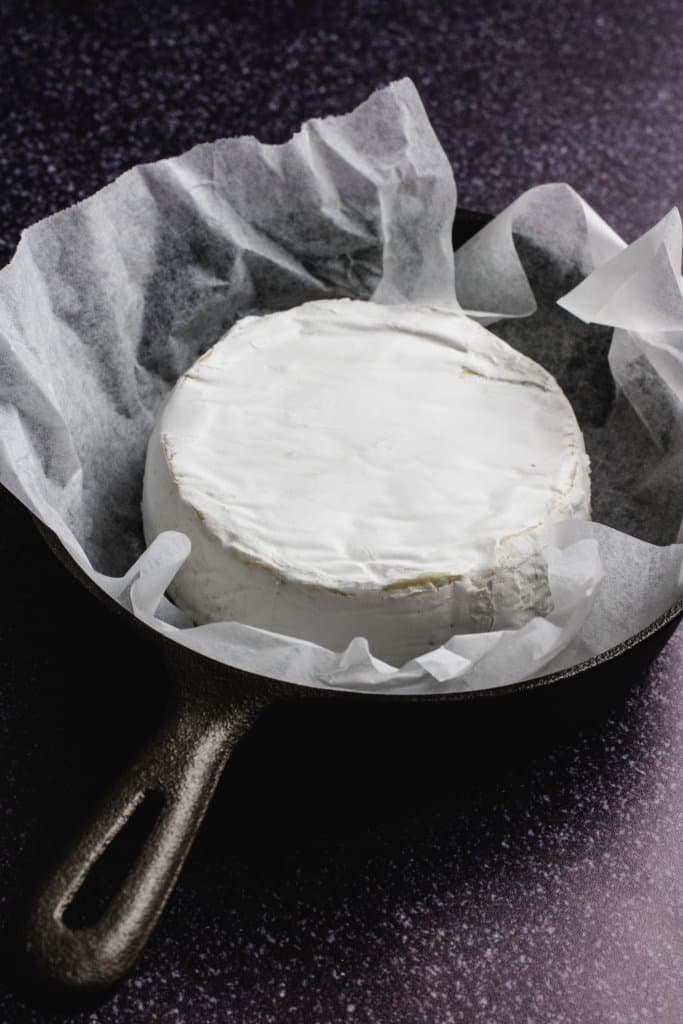 A wheel of camembert on some baking paper inside a black cast iron skillet on a black speckled background.