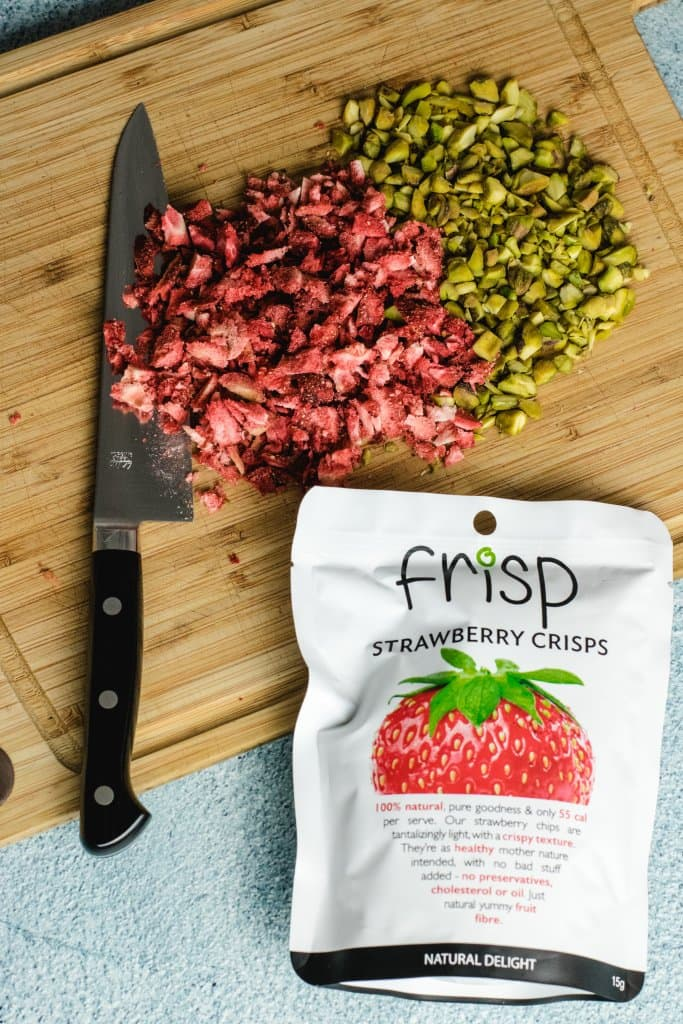 Knife on a bamboo chopping board with chopped freeze dried strawberries and chopped pistashios with a frisp strawberry crisps packet