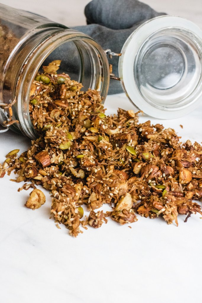 keto granola tipping out of a glass jar with lid