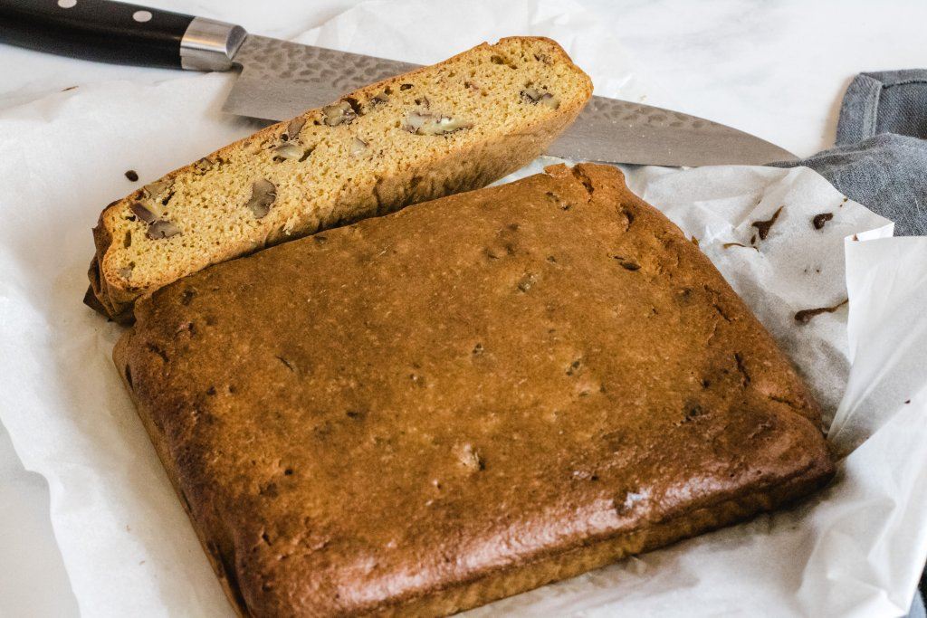 Slab of keto blondie sitting on baking paper with one strip cut and the cut side facing up. A large knife is sitting next to the blondie