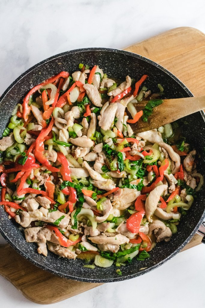 Keto chicken stir-fry in a large frying pan on a wooden chopping board