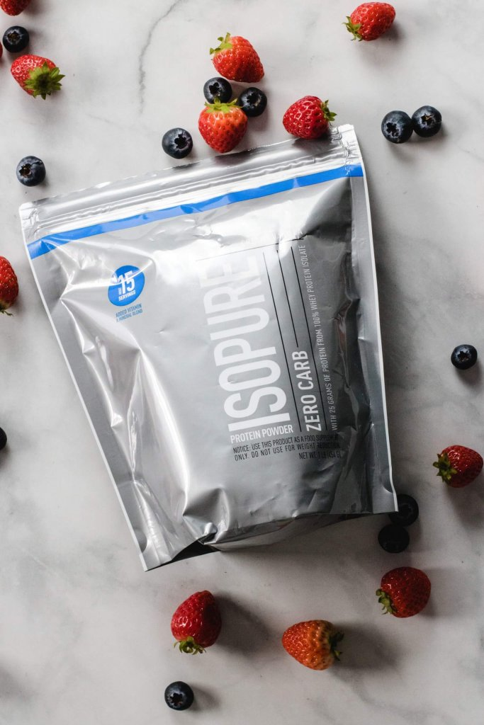 Packet of isopure protein powder with blueberries and strawberries scattered around