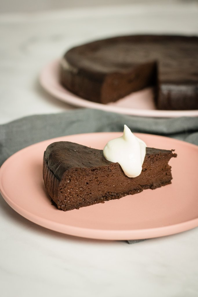 A slice of keto flourless chocolate cake with a dollop of cream on a pink plate with the rest of the cake in the background