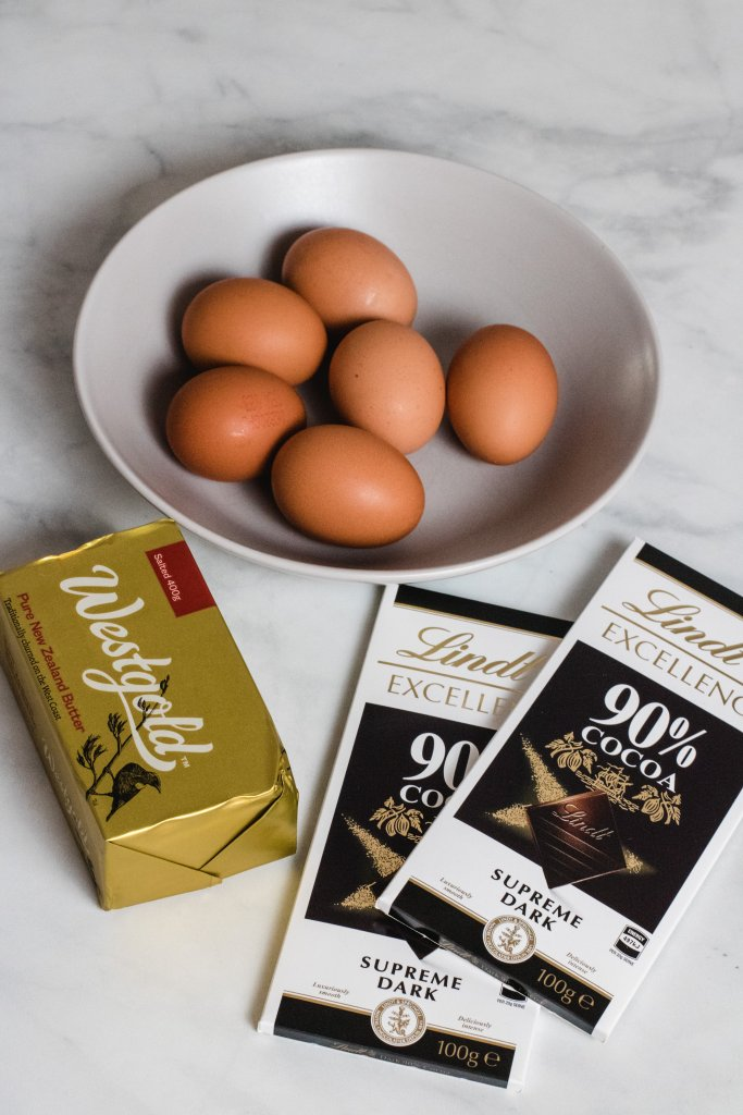 cake ingredients - 6 eggs, butter and 90% dark chocolate on a white marble background