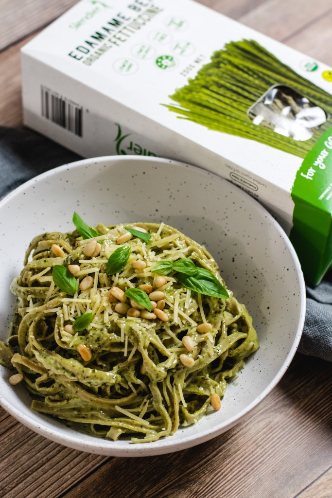 Keto cream pesto pasta in a white speckled bowl, topped with basil leaves and pine nuts, with a box of edamame pasta next to it on a wood panel background.