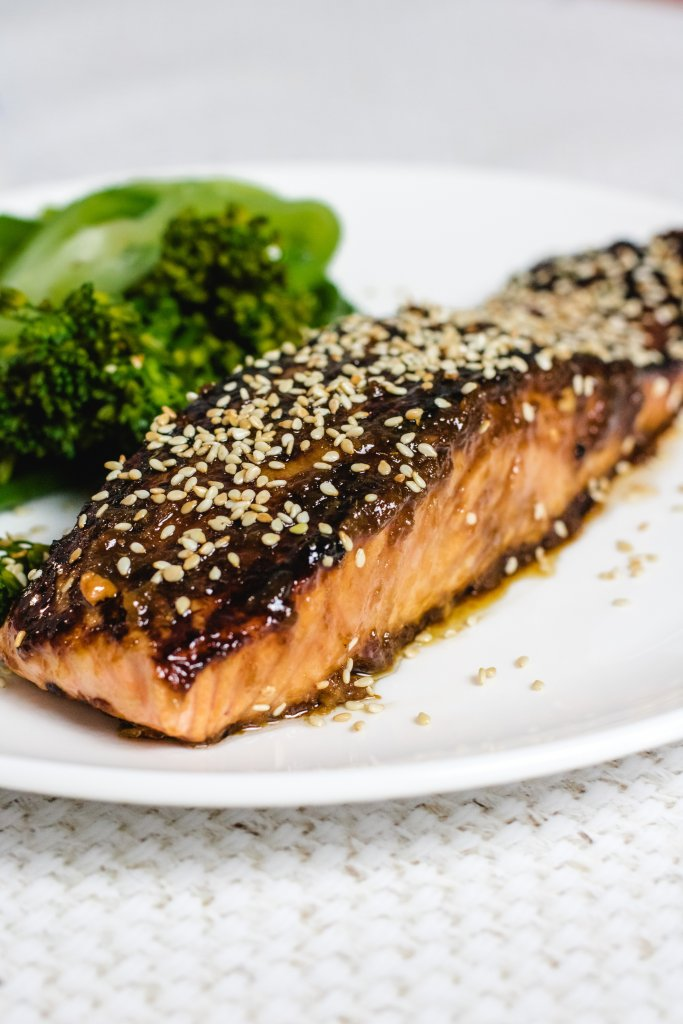 1 keto teriyaki salmon fillet on a plate with some steamed brocolini and pak choy on a white plate