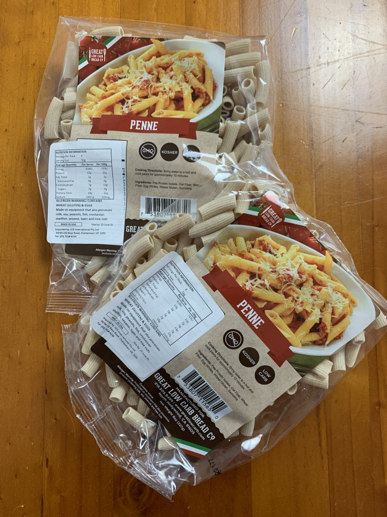 two packs of great low carb bread co penne pasta on a timber background