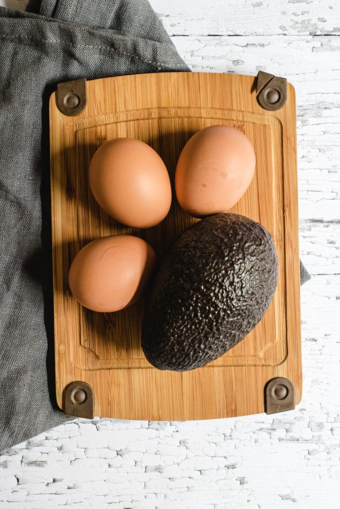 3 hard boiled eggs, 1 whole avocado sitting on a wooden board with a white wooden background