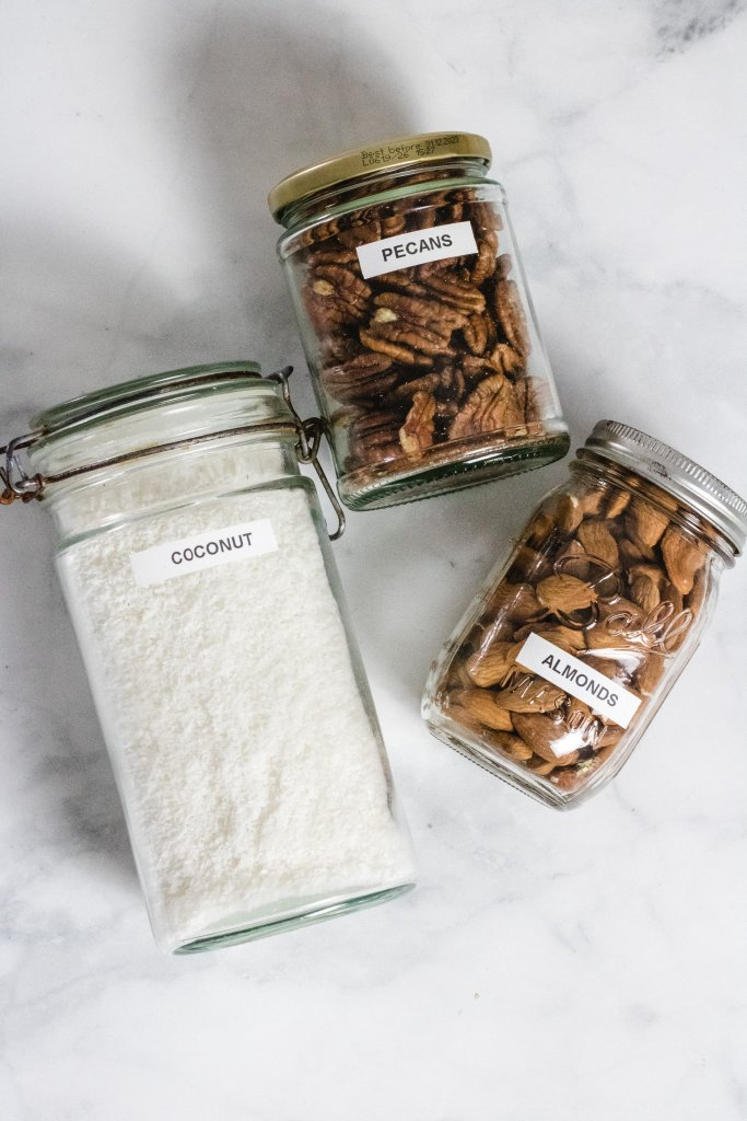 Coconut, almonds and pecans in jars on a marbeled background