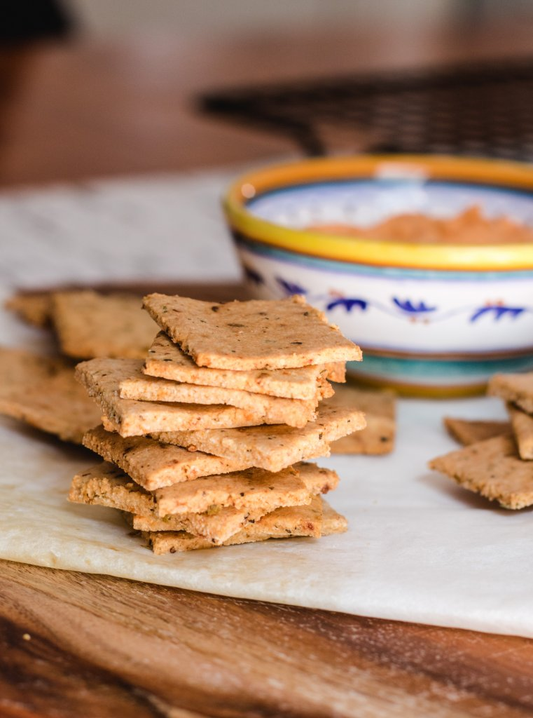 Keto crackers stacked into a tower with others scattered around and a bowl of capsicum dip in the background