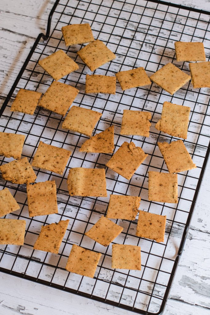 Keto crackers on a black cooling rack with a white timber background