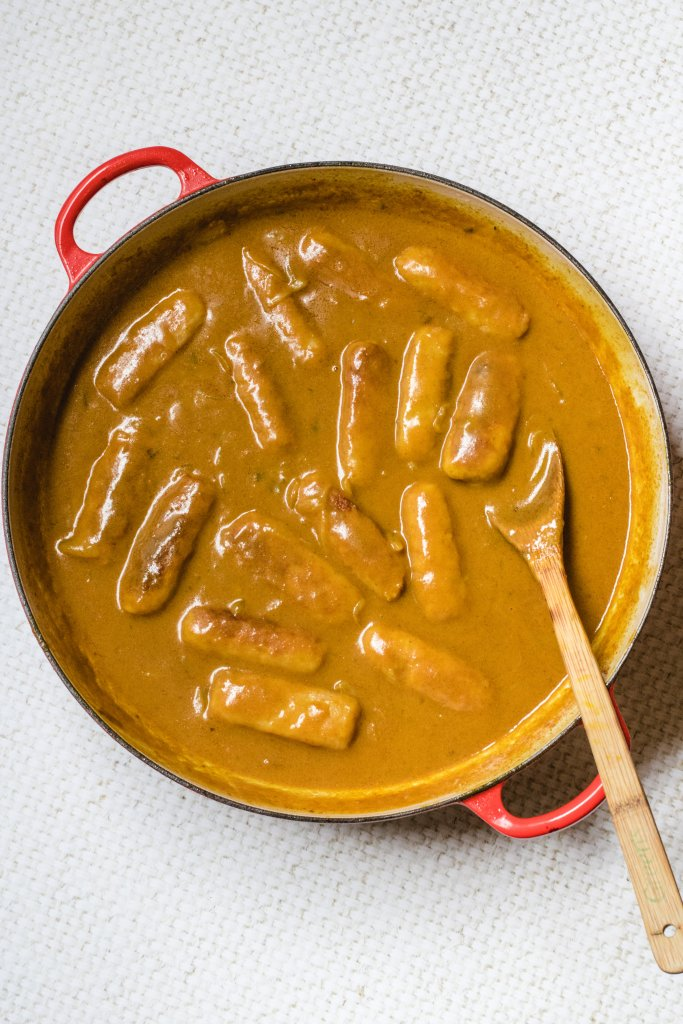 Keto curried sausages in a red pan ith a wooden spoon in it