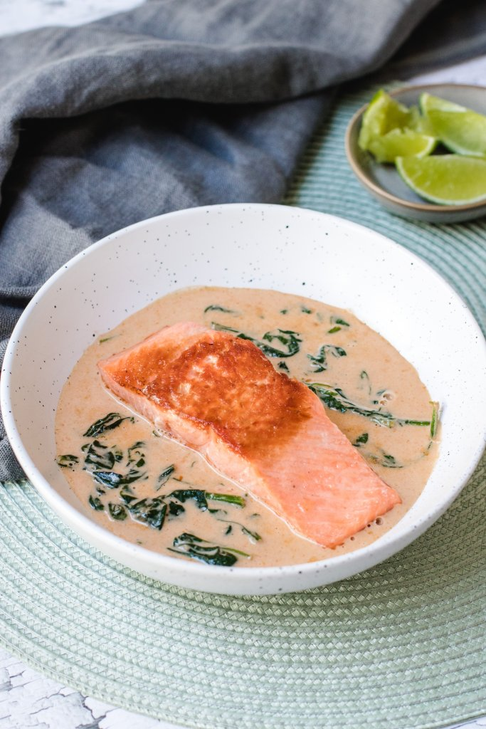 Pan fried salmon in curry sauce in a white speckled bowl, on a green placemat with a grey linen tea towel and a small bowl of cut lime around it.