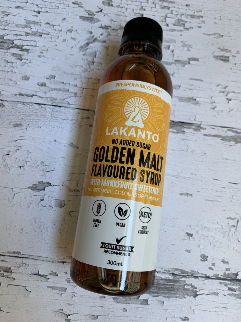 A bottle of Lakanto golden malt flavoured syrup on a white wood background
