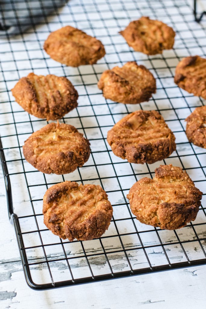 10 Anzac biscuits on a black cooling rack on a white wood background