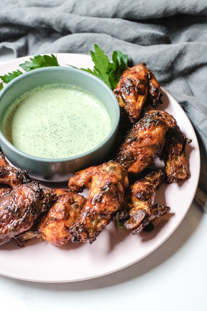 A close up photo of a pink plate filled with tandoori chicken wings with a bowl of yoghurt sauce in the middle of the plate and some green herbs.