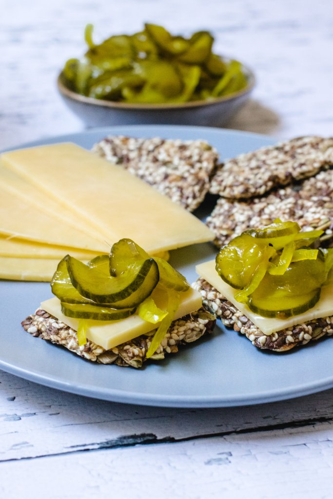 A blue plate with seed crackers, cheese and pickles with a small bowl of pickles in the background