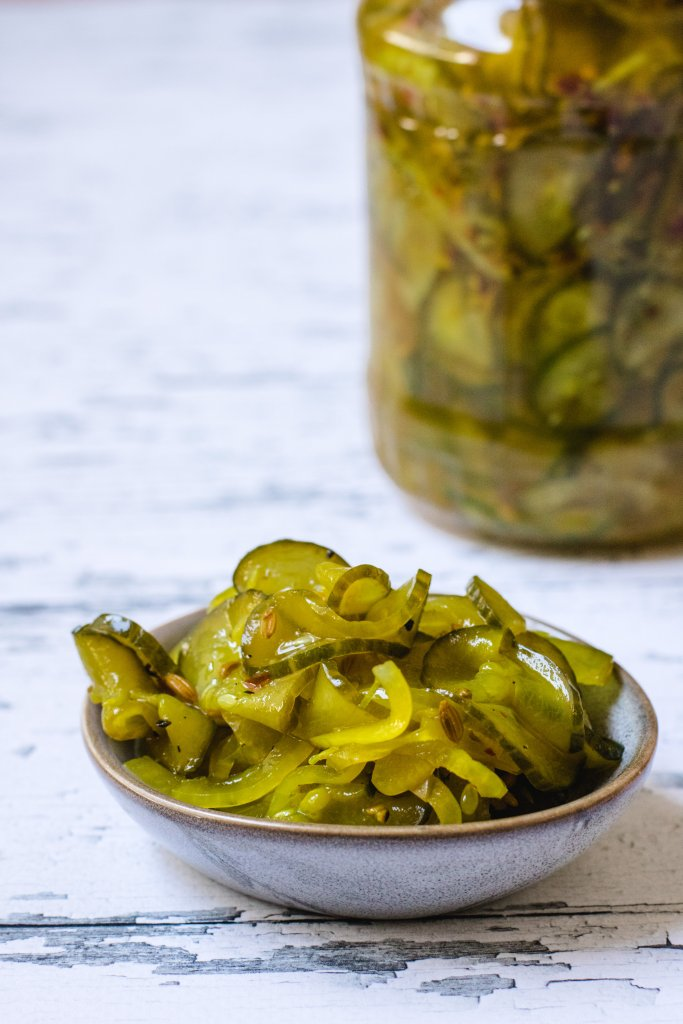 A small bowl of pickles on a white wood background with a large jar of pickles in the background.